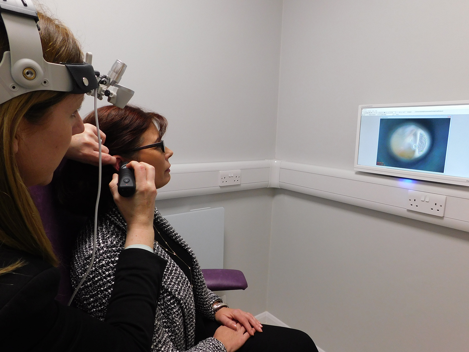 Catherine Steed showing client her internal ear with video otoscope